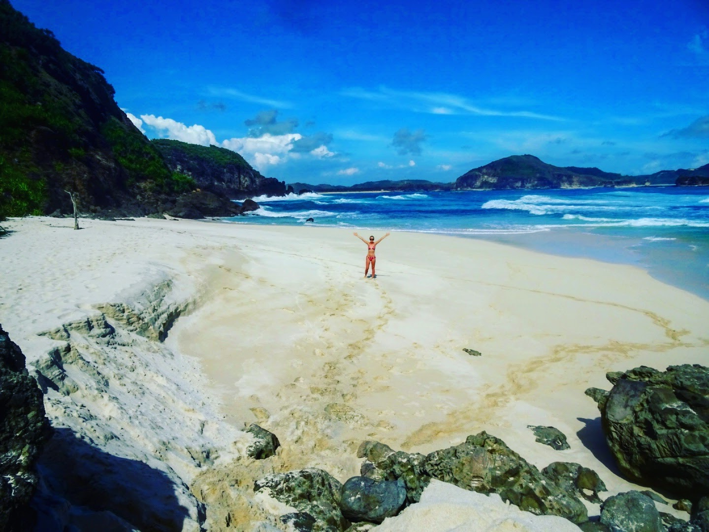 Nicola standing in the middle of an empty beach by the sea in southern Lombok, Indonesia.
