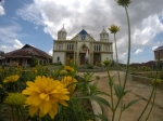 A huge church with bright yellow flowers in front of it and a large statue of Jesus.