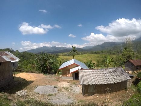 Four tin houses above a vast paddy field with rows of mountains in the distance.