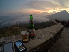 A kindle, phone and beer pictured with the volcano in the background.