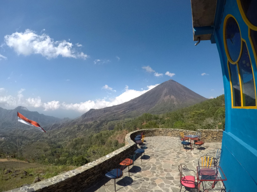 Tables and chairs from a restaurant in front of a volcano with the Indonesia flag alongside.