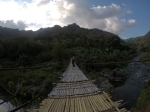 A long bamboo bridge across a river.