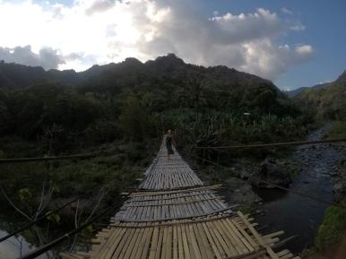 A long bamboo bridge across a river.