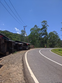 A road with three wooden stalls selling fruit and vegetables.