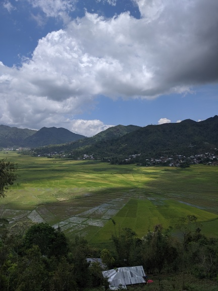 A photo looking down on to Lingko Paddy fields near Cancar in Flores. The shape of the fields is like a pie chart, with mountains and villages in the distance.