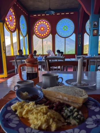 a plate of breakfast with stained glass windows behind