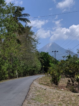 A road leading to a volcano which has smoke coming out od it