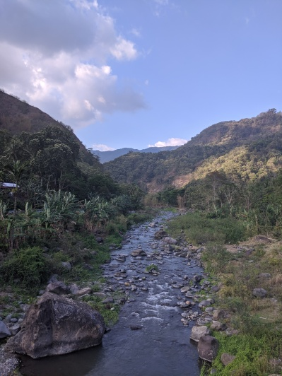 A river running through a valley of mountains on either side