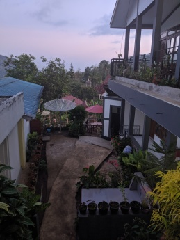 Looking through the middle of a homestay with rooms on the right and two family graves below.