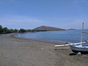 a beach with very dark sand, the ocean to the right, a white boat also on the right and a small hill in the distance