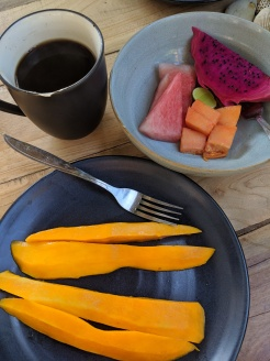 breakfast dishes full of colourful fruit alongside a cup of coffee