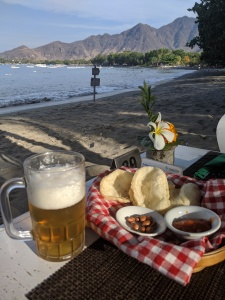 a beer and a plate of food on a table at a restaurant which is on a beach, right next to the sea