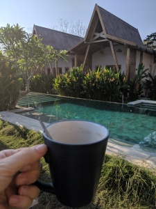 a cup of coffee held in front of a long swimming pool
