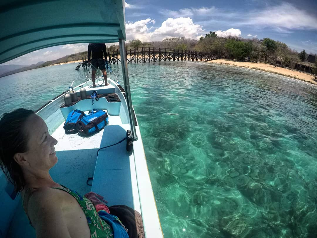 I'm on the left sat inside a dive boat which is pulling up to a pier in West Bali National Park, the ocean is sparkly and turquoise